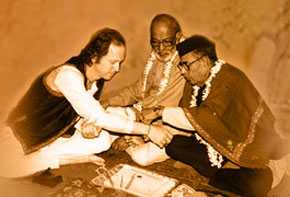 Ustad Mushtaq Ali Khan ties the traditional thread (gandha) which binds the relationship between master and student. The renowned D.T. Joshi, disciple of Enayet Khan, looks on